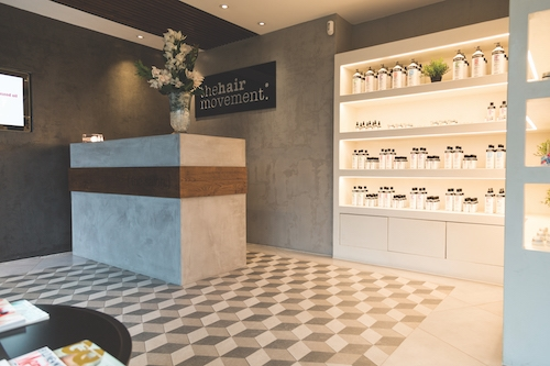 Concrete reception desk, concrete welcome wall, black concrete feature wall in hairdresser saloon